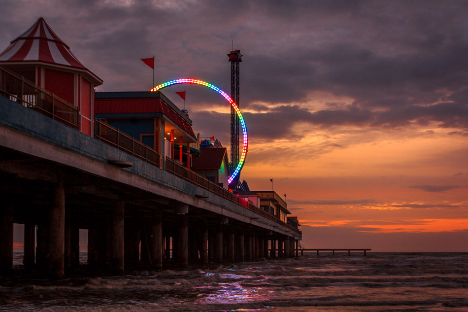 The rainbow-colored lights of a thrill ride on Galveston, Texas' Pleasure Pier pierce the dawn's twilight.