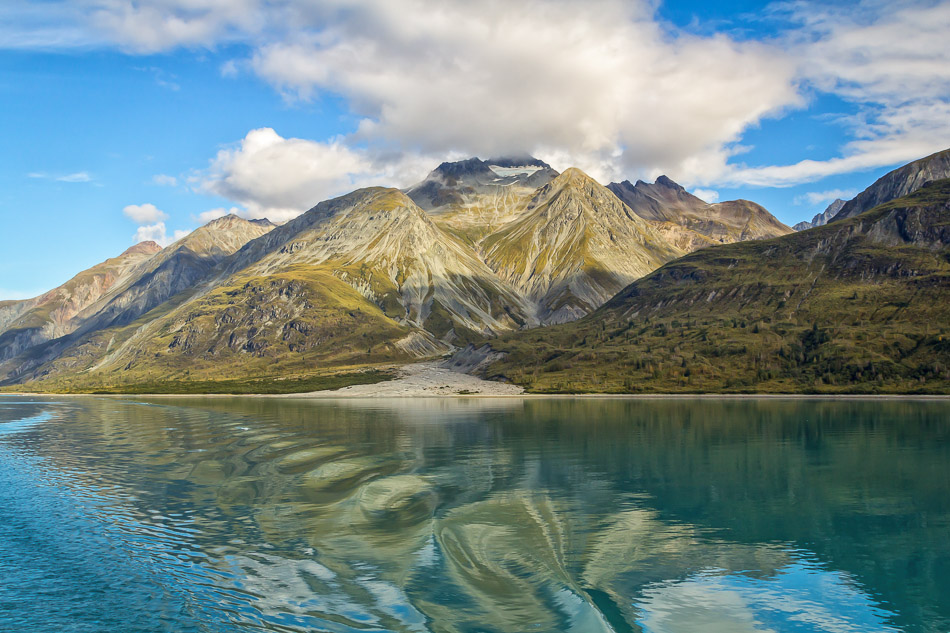 A cloud envelops a small-glacier-topped mountain in Alaska's Glacier Bay National Park.